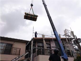 クレーンで資材を屋根の上に運ぶ